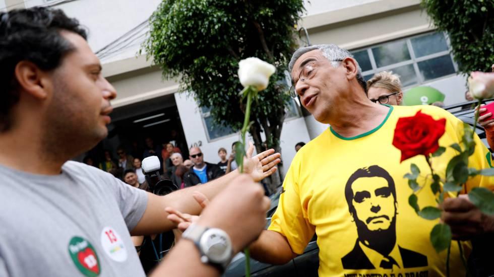 Um eleitor de Fernando Haddad oferece uma flor a um eleitor de Jair Bolsonaro