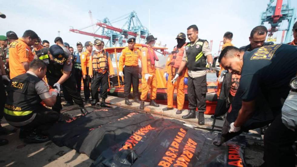Equipes de resgate com corpos de algumas das vítimas. Reuters