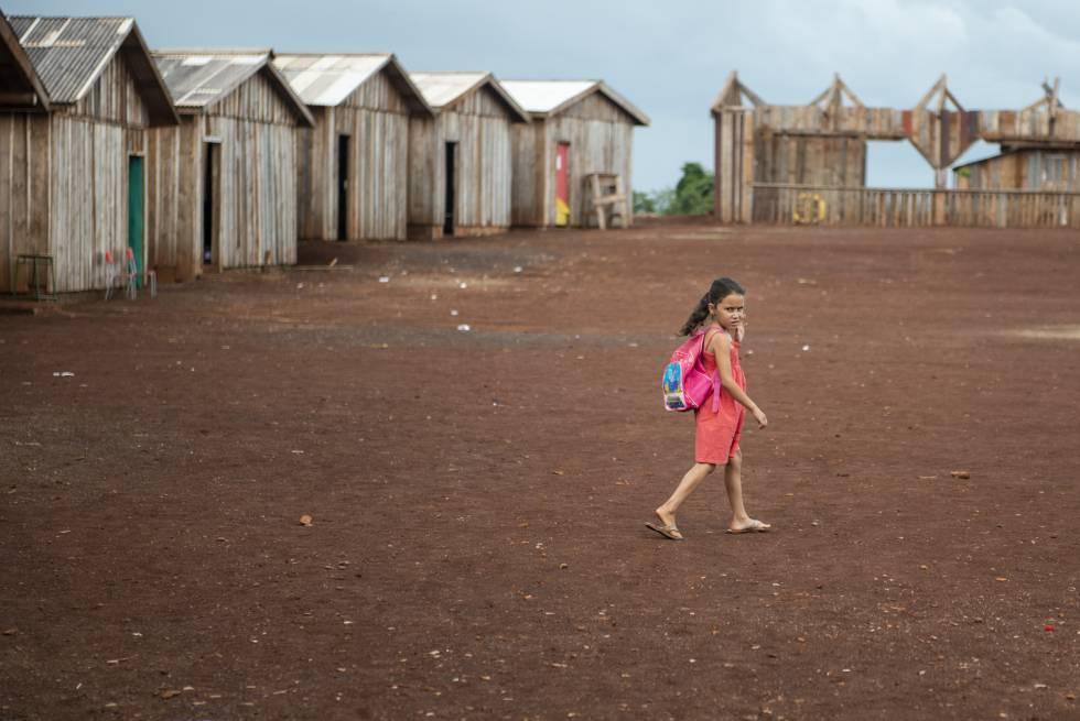 Uma menina caminha em direção a sala de aula, na escola itinerante Herdeiros do Saber.