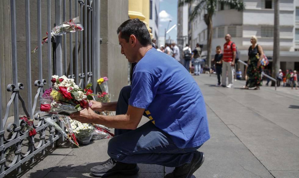 Um homem deixa flores para as vítimas da Catedral de Campinas.
