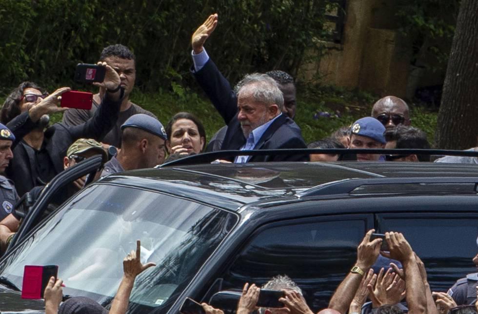 Lula acena a apoiadores na saída do cemitério.