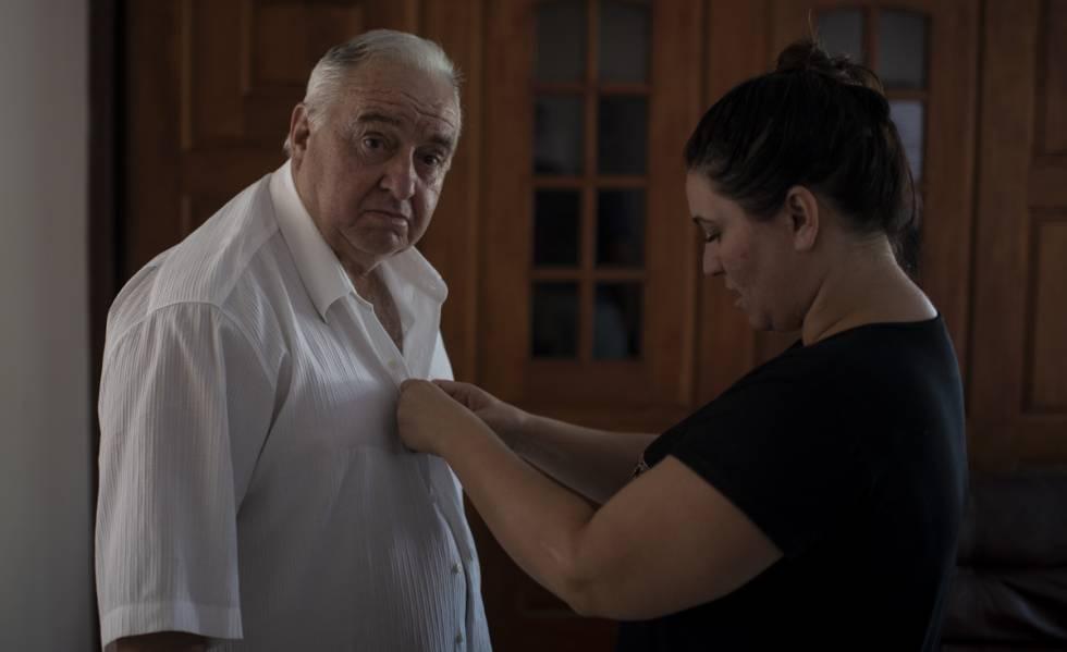 Carminha arregla la camisa de su padre para la entrevista.