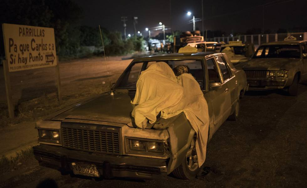Um homem dorme sobre seu carro enquanto espera por gasolina em Maracaibo.