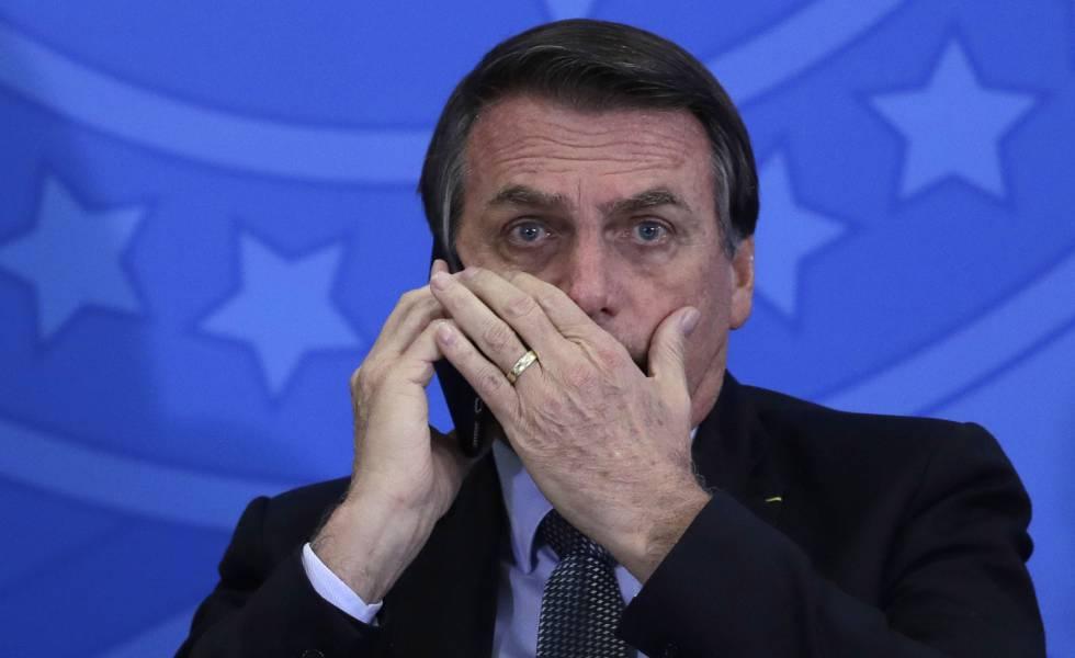 Jair Bolsonaro fala ao celular durante cerimônia no Palácio do Planalto.