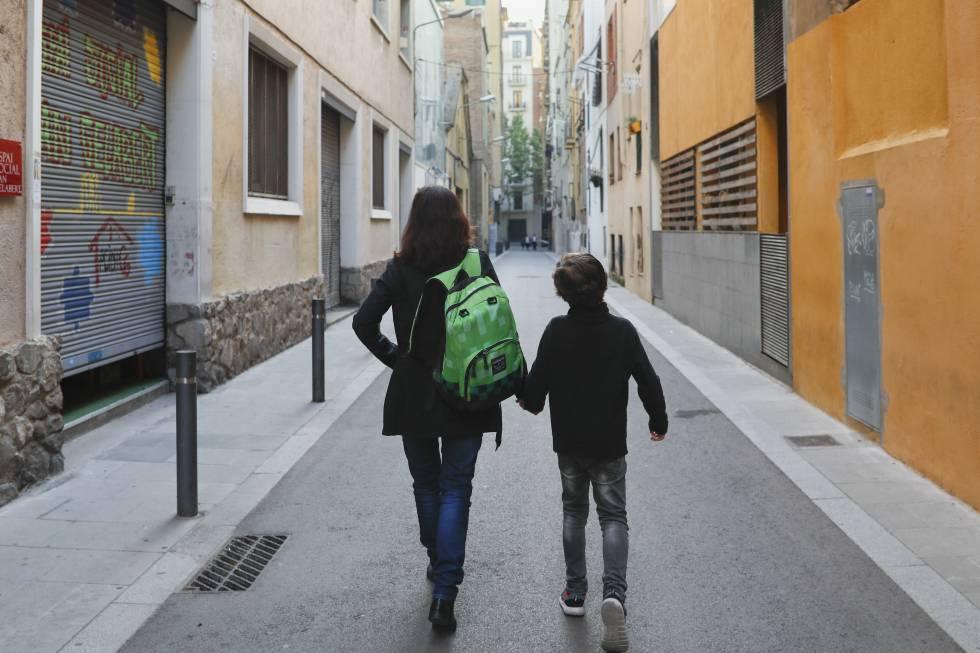 Una madre carga con la mochila de su hijo camino de la escuela.