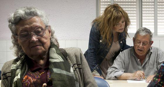 Raquel ayuda a su padre enfermo de Alzhéimer, en un taller de la asociación de familiares.