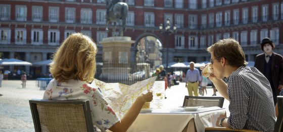 Two visitors to Madrid enjoy a drink in the sunshine of Plaza Mayor - but is anyone relaxing with a coffee?