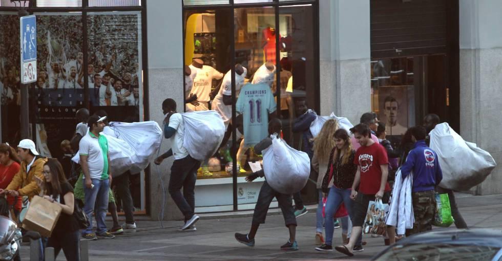 Unos manteros recogen su mercancía en el centro de Madrid.