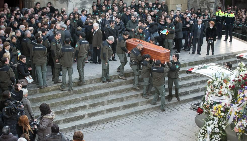 Compañeros de los agentes trasladan el féretro de una de las víctimas en su funeral.