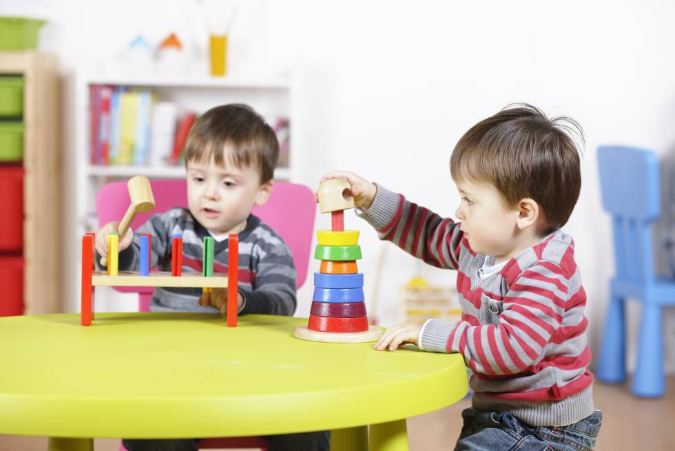Dos gemelos juegan en clase.