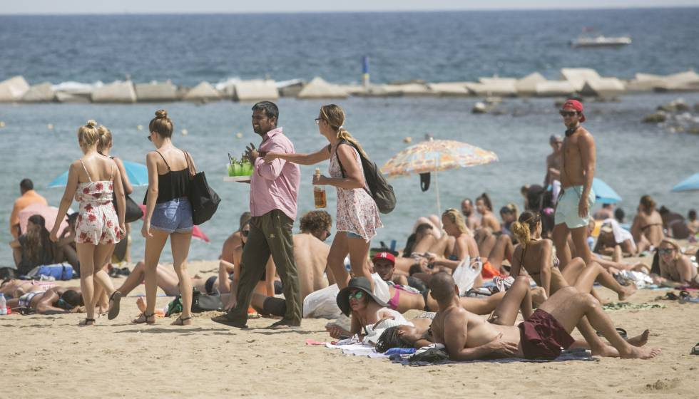 A Plain Clothes Police Officer Stops Vendor On The Barceloneta Beach Wednesday