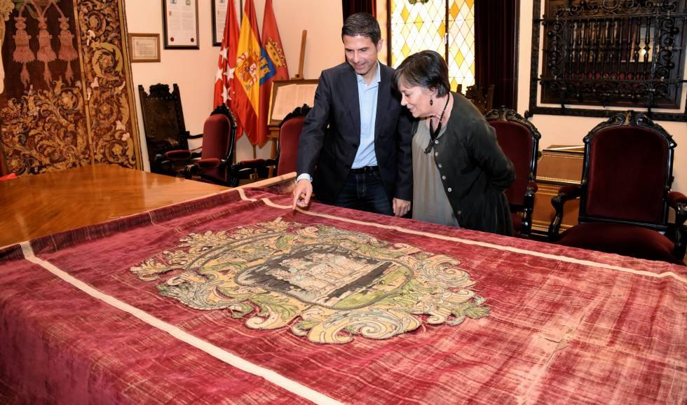 El alcalde de Alcalá, Javier Rodríguez Palacios, y la concejal de patrimonio histórico, Olga García, observando el tapiz del siglo XVII.