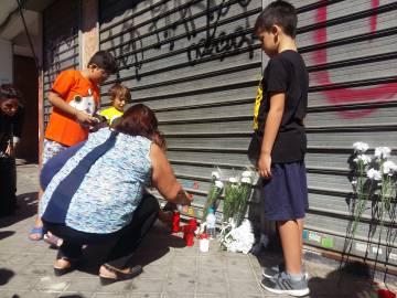 Varios vecinos encienden velas en la puerta del establecimiento donde murió el niño de tres años.