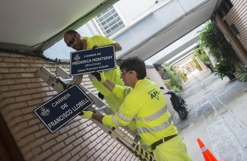 Dos operarios municipales cambian las placas de una de las calles.