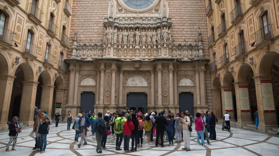 Varios turistas y feligreses congregados frente las puertas del Monasterio, de Montserrat.