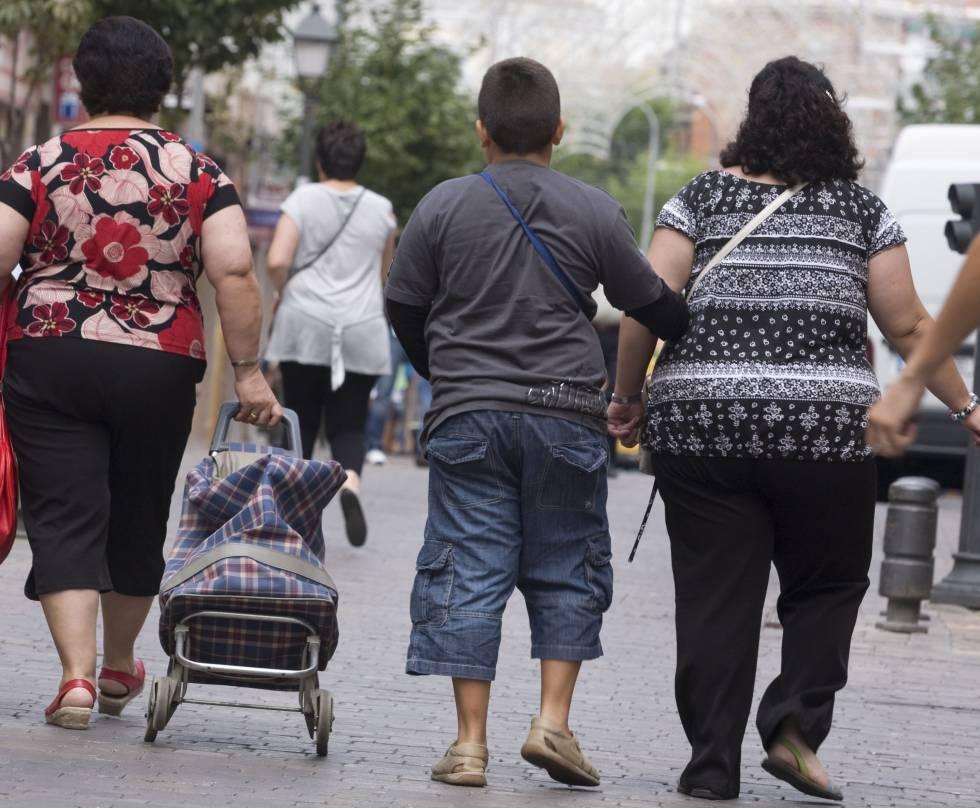 Una madre y su hijo con sobrepeso caminan por una calle de Madrid.