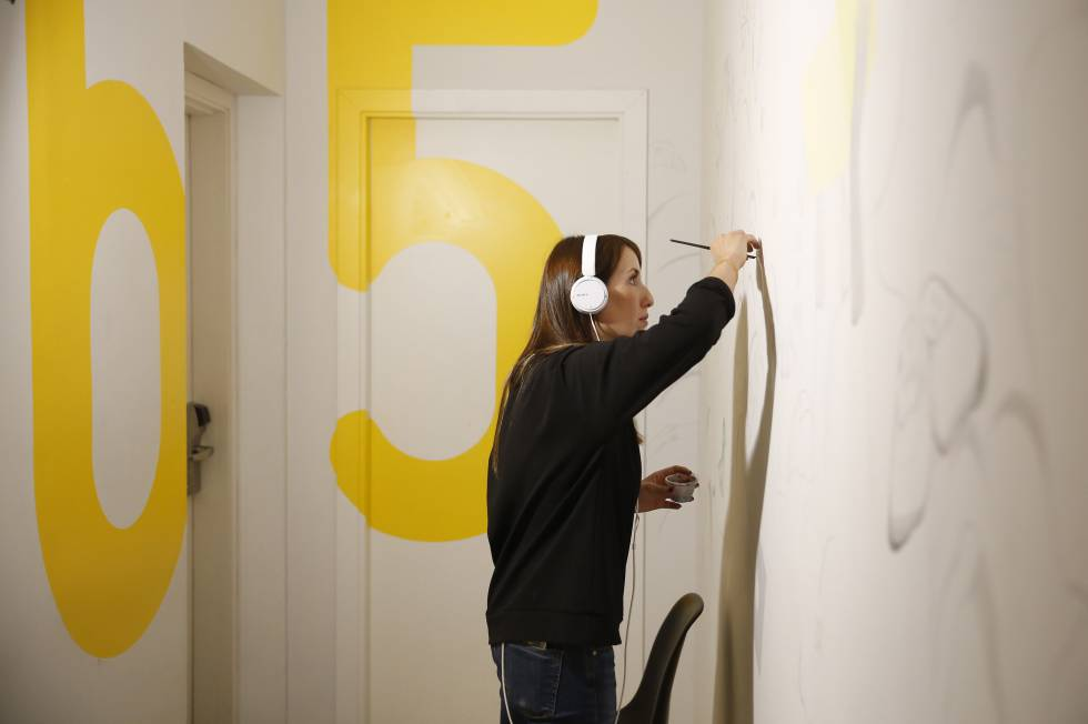 Una de las artistas trabajando en una pared del establecimiento.