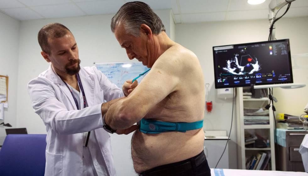El doctor Jorge Pagola, investigador del VHIR, coloca al paciente Meriton Bacuña, un chaleco Holter que registra la actividad del corazón