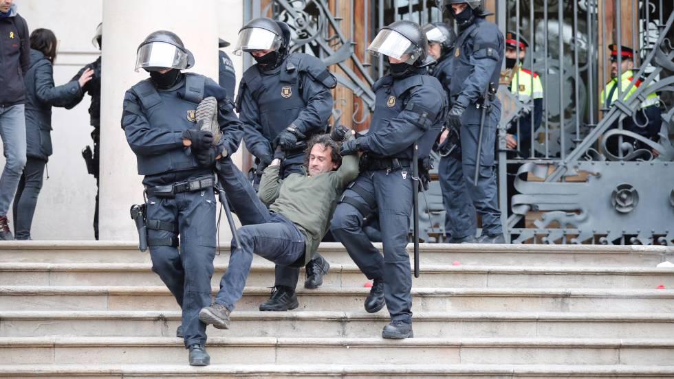 Agentes antidisturbios desalojan a uno de los manifestantes.