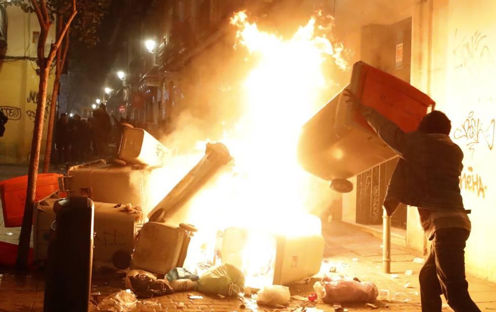 Un hombre incendia contenedores en la calle Mesón de Paredes, en Lavapiés.