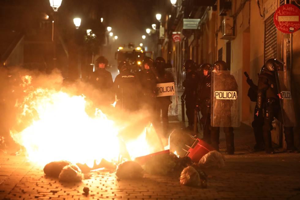 Contenedores incendiados frente a un cordón policial, en la calle Mesón de Paredes.