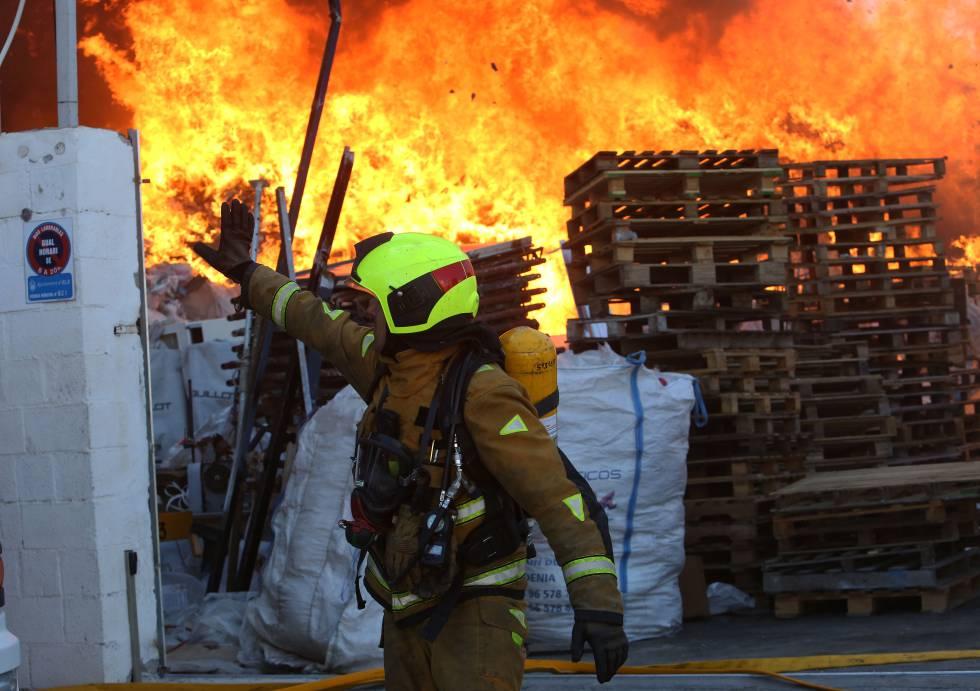 Un bombero en el incendio que se ha declarado en un almacén de Elche.