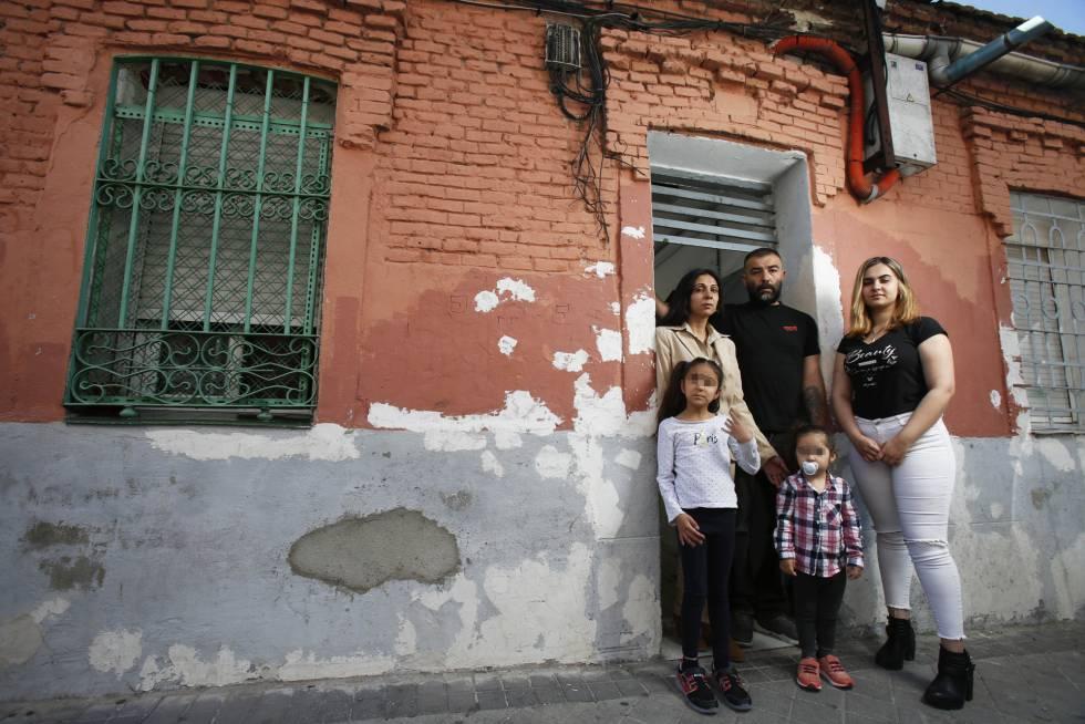 La familia, fotografiada frente a la puerta de su vivienda, en Vallecas.