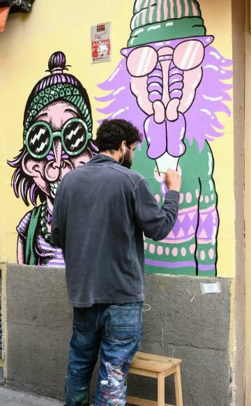 El artista Ramón Amorós dibujando a los 'mandrileños' en la Calle Argumosa.