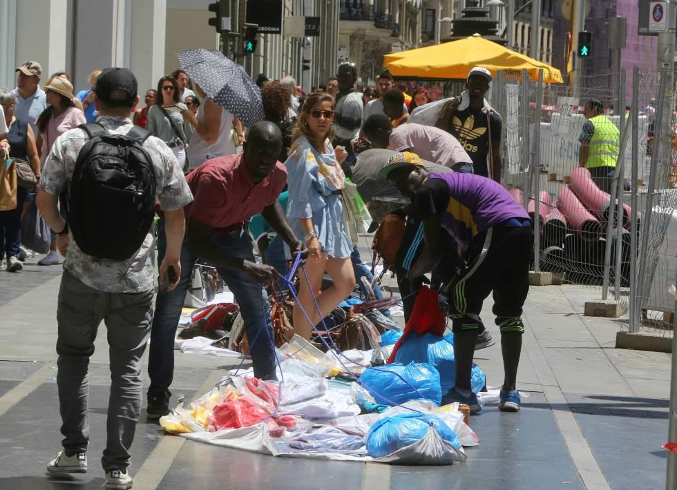 Los manteros recogen sus sábanas delante de un conocido comercio de Gran Vía.