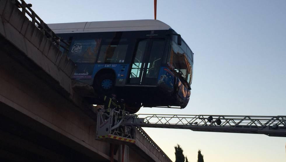 Los bomberos aseguran la parte del autobús que ha quedado colgado del puente.