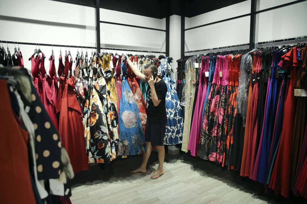 3f65f81bd Un dependiente del mayorista Albano s coge un vestido para un pedido en la  tienda de Tirso