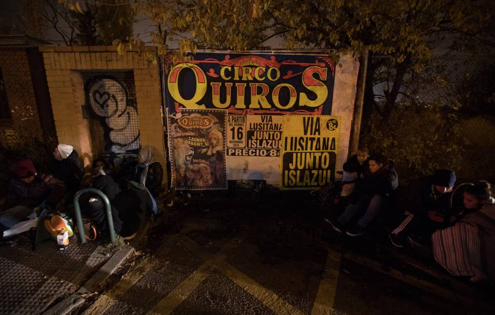 Migrants wait in line outside the Aluche police station.