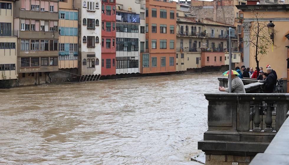 Varias personas contemplan el paso del río Onyar, desbordado por el temporal de lluvias.
