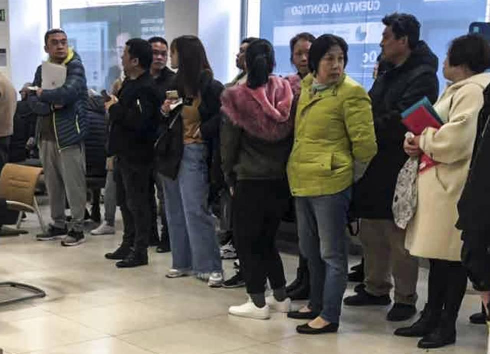 Chinos afectados por los bloqueos de cuentas hacen cola en una sucursal del BBVA en Usera, Madrid.