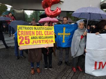 Familiares de los fallecidos en el crimen del Cash Record de O Ceao, con un cartel de protesta, y una bandera de Asturias, donde De Lara también investiga la corrupción.
