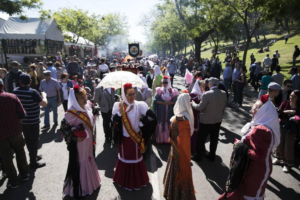 Una mujer sostiene un parasol vestida de chulapa junto a otras compañeras.