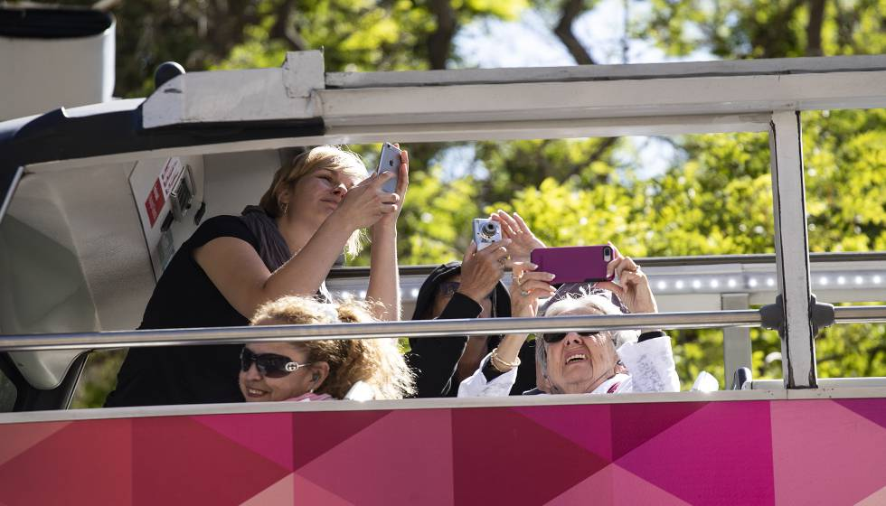Turistas haciendo fotos en la Sagrada Familia desde un autobús.