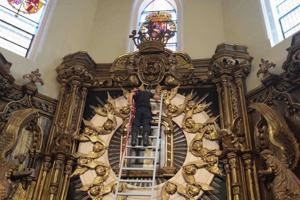 El bombero Felipe García baja el cuadro de la Virgen de La Paloma.