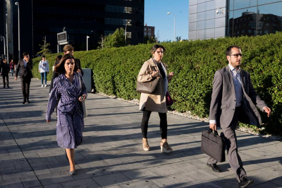 Trabajadores llegan a las oficinas de las Cuatro Torres este miércoles por la mañana.