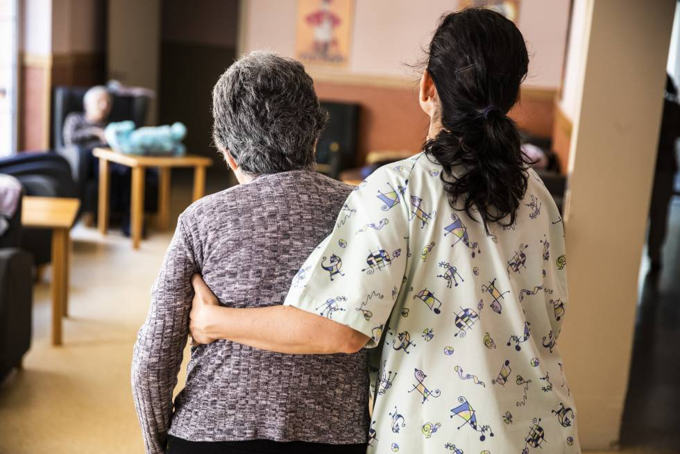 Una cuidadora acompaña a una persona mayor en una residencia geriátrica en un pueblo de la región.