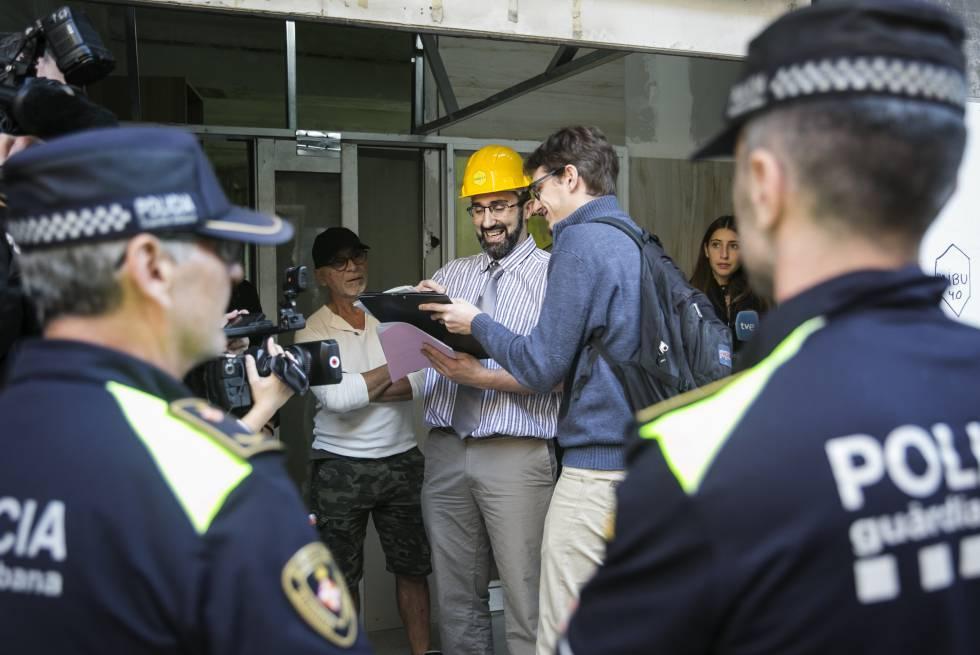 Los dos socios de Haibu 4.0., Eduardo Jausi (alias Eddie Wattenwil), con gorra negra; y Marc Olivé, con casco amarillo, durante el precinto de su piso colmena por parte de la Guardia Urbana de Barcelona, el 22 de octubre de 2018.