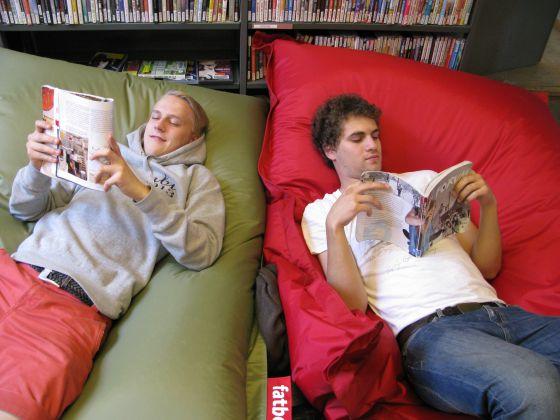 Dois jovens leem deitados na Biblioteca 10, em Helsinki (Finlândia).