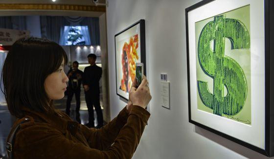 Una visitante a la casa Christie's fotografía una obra de arte.