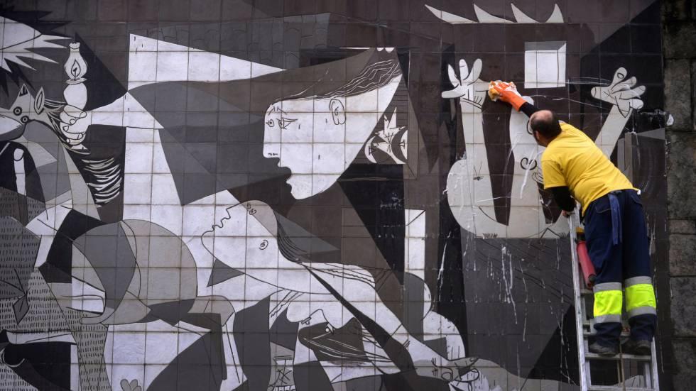 Un trabajador municipal limpia una reproducción de 'El Guernica' de Picasso en Guernica (País Vasco).