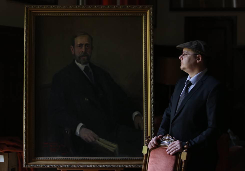 El pintor Alejandro Cabeza junto al último retrato que ha pintado, el del geólogo Lucas Mallada, en el Museo Geominero de Madrid.rn
