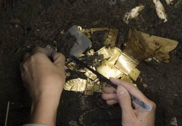 El chimali, entre otras piezas de oro, bajo la tierra húmeda