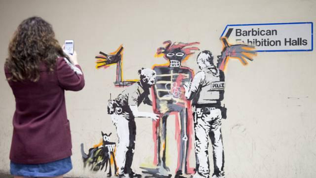 Una foven toma una foto de uno de los dos murales de Banksy.