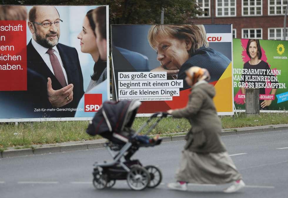 Propaganda electoral en una calle de Berlín con tres de los candidatos que se presentan a la elecciones de este domingo.