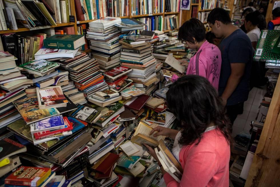 Varios clientes buscan libros en A través del espejo.