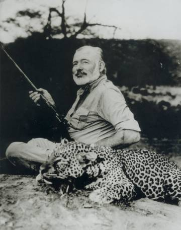 Ernest Hemingway stands beside a dead leopard in 1953.